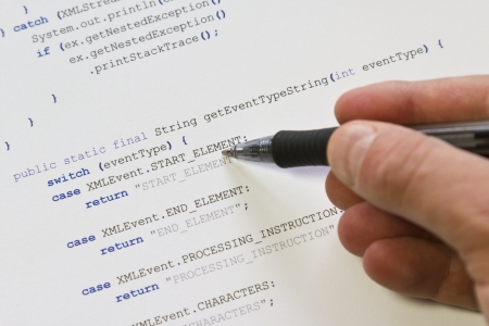 A programmer   man pointing with his pen at Java computer code  Software   application program code  XML parser  Stock Photo - 19198262