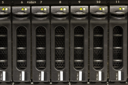 A disk cabinet   SAN with many large hard drives mounted in a rack  Shot in a data center  photo