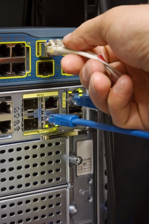 Insert  patching a fiber cable into a switch in datacenter  The visible components are a fiber   Cat 5 switch and a high end router for gigabit network