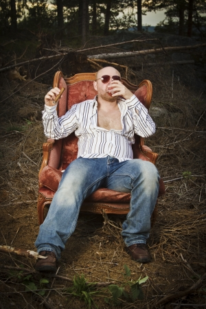 35 years old: Sleazy man   dude in a classic vintage chair in the middle of a logging area  Smoke a cigar and drinking Cognac in woods  Stock Photo