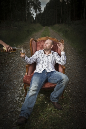 Sleazy man in a classic vintage chair in the middle of a road in the woods  Smoking cigar and get served Cognac from a woman  Stock Photo - 19198800