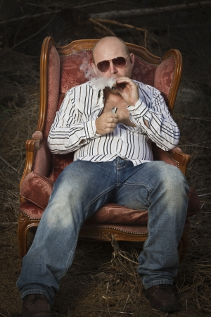 sleazy: Sleazy man   dude in a classic vintage chair in the middle of a logging area  Fire up and smoke a cigar and drinking Cognac in woods