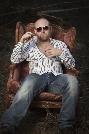 35 years old: Sleazy man in a classic vintage chair in the middle of a logging area  Smoking cigar and drinking Cognac in woods