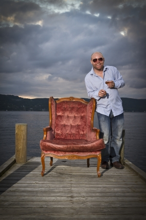 35 years old: Happy celebrateing man in a classic vintage chair on a pier with water and sky in the background  Smoking cigar and drinking Cognac