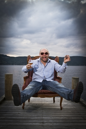 35 years old: Happy celebrating man in a classic vintage chair on a pier with water and sky in the background  Smoking cigar and drinking Cognac