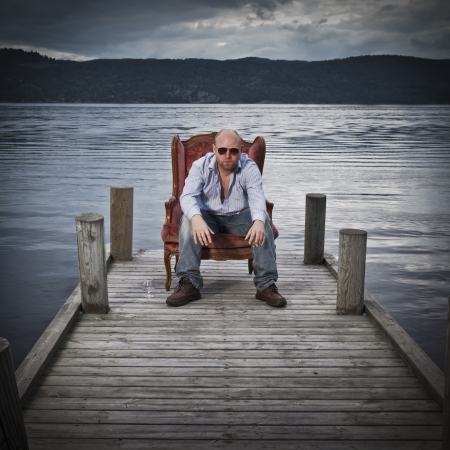 Sleazy man in a classic vintage chair on a pier with water and sky in the background  Smoking cigar and drinking Cognac  photo