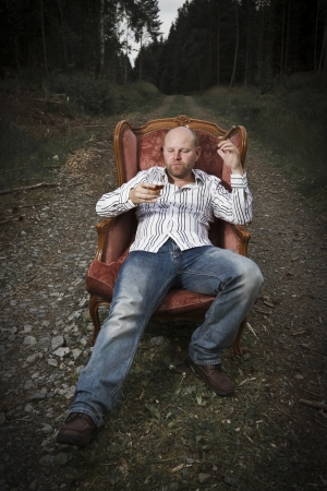 35 years old: A thoughtful man   guy drinking cognac and smoke cigar in a vintage chair in the middle of a road in woods