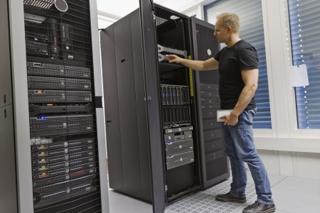 it technology: It engineer   consultant working in a data center  Holding a hard drive and opning a server