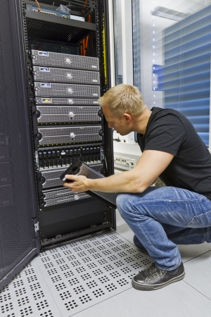it tech: It engineer   consultant working in a data center  Holding a disk cabinet front and look at the disks  This enclosure in a SAN  storage area network   Stock Photo