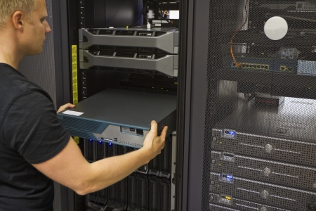 It engineer   consultant install   inserts a router   switch in a rack  Shot in a data center