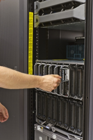 it technician: IT technician   consulant insert   remove a harddisk from a blade server in a data center  This is a 2,5  SAS harddrive  Stock Photo