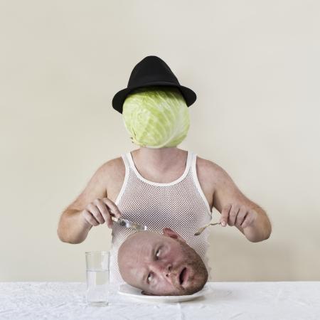 wierd: Wierd cabbage man with hat eating a mans head on a plate