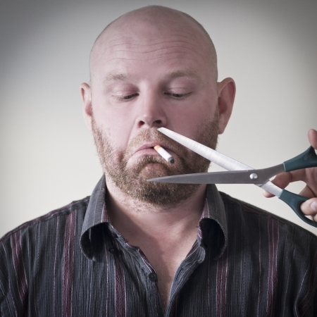 quitting: A scissors cuts the cigarette to a smoking man  Trying to quit smoking