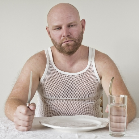 25 years old: Hungry man with no food on his plate  Perphas on a diet  Stock Photo