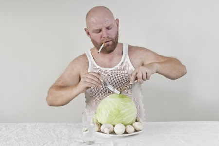 wierd: Wierd man eat cabbage and mushrooms while smoking a cigarette