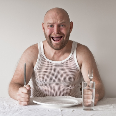 25 30 years old: Strange and hungry man with no food on his plate  Perhaps on a diet