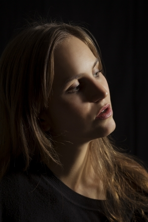 light source: Studio shot of a young woman   girl with attitude with lowkey lighting  Black background