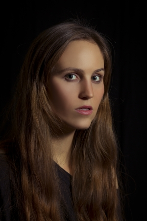 lowkey: Studio shot of a young woman   girl with lowkey lighting  Black background  Stock Photo