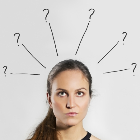 Young woman   girl thinking   wondering with gray background  Question marks over her head  photo