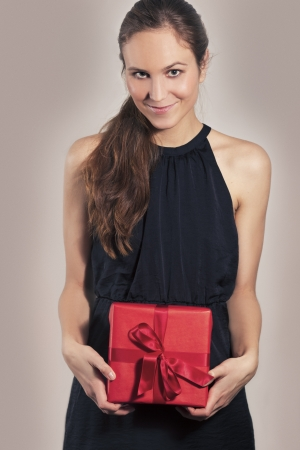 women s fashion: Excited young attractive woman with christmas gift or birthday present  Gray and red background  Stock Photo
