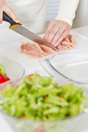Young woman in a white kitchen cut chicken meat fillet  Vegetables  photo