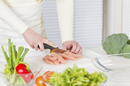 Young woman in a white kitchen making a chicken meat fillet dish  photo