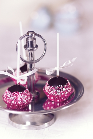 atilde: Chocolate cake pop decorated with pink and white sugar sprinkles