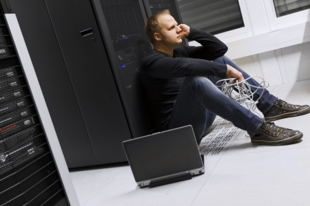 apathetic: Frustrated and exhausted it engineer   consultant in a data center  Sitting apathetic in front of a server rack  Stock Photo