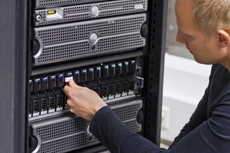 It engineer   consultant working in a data center  This enclosure is a SAN  storage area network  and servers at the top
