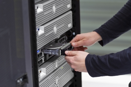 It engineer   consultant working in a data center  Install a new harddisk in a rack server  Stock Photo