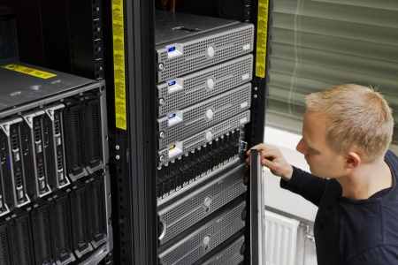 enclosures: It engineer   consultant working in a data center  This enclosures is a SAN  storage area network  and servers at the top