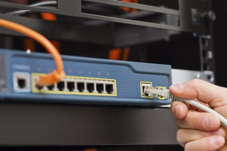 Close up of a IT consultant inserting   connecting a network cable into a switch  photo
