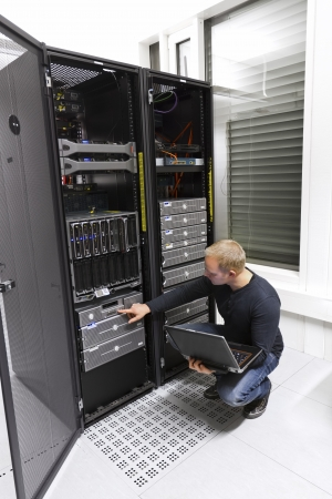 data center: It engineer   consultant working in a data center  Maintain backup  Monitoring with laptop  Stock Photo