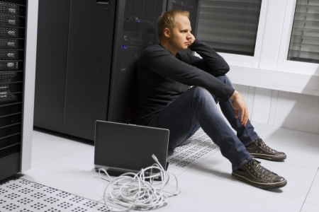 Frustrated and exhausted it engineer   consultant in a data center  Sitting apathetic in front of a server rack  photo