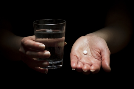 Woman holding a glass of water and pill  Take a pill  Medication photo