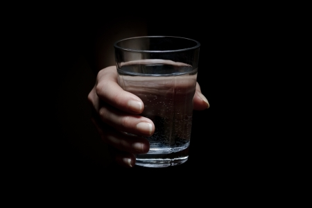Water glass: Woman holds a glass of water  Give a glass of water  Drink more water  Black background