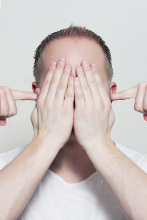 wierd: A man with hands in front of his eyes and fingers in his ears  Try to hide
