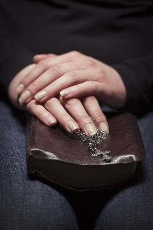 A close-up of a christian woman pray  Holding a Cross over a bible  photo