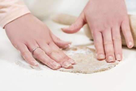 flatten: Girl baking and roll dough  Making fajitas or pizza  Spelt whole grain flour on the table