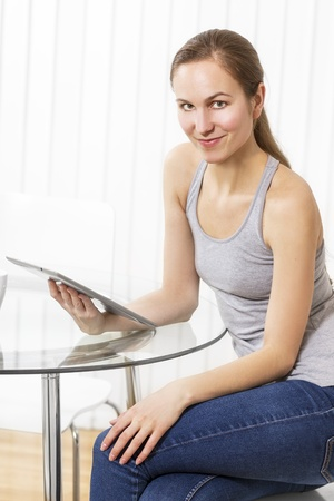 tank top: Woman drinking coffee and using pad in white exclusive kitchen