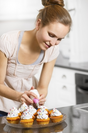 baking cake: A woman baking muffins or cupcakes in white kitchen