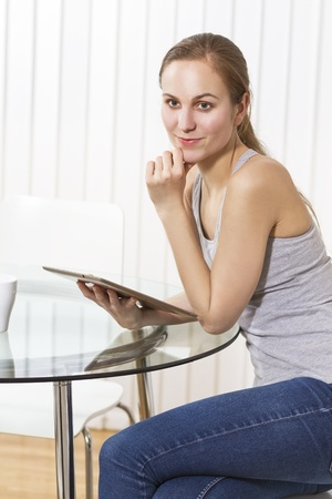 Woman drinking coffee and using tablet in white exclusive kitchen  photo