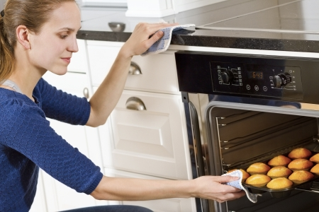 baking oven: A woman making muffins in white kitchen  Stock Photo