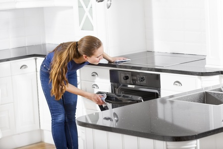 baking oven: A woman bake and cook in white kitchen  Stock Photo