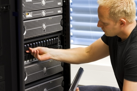 technicians: It engineer   consultant working in a data center  This enclosure is a SAN  storage area network  and servers at the top