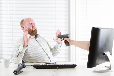 threatened: Office worker robbed and threatened by the computer  Internet fraud  Stock Photo