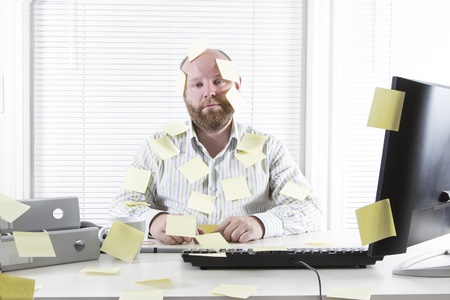 Exhausted and tired office worker in the office  To much work and no motivation  Place your own text on the notes  Stock Photo