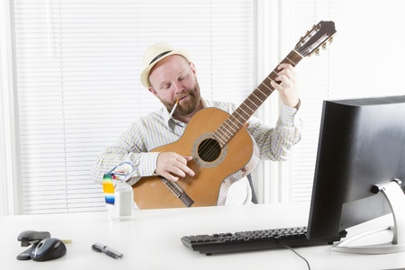 One happy office worker drinking, playing guitar and smoking in his office  photo