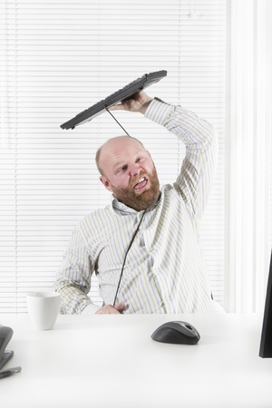 self harm: Office worker   businessman strangle himself with his keyboard cable Stock Photo
