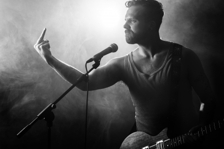 Young man gives finger to the audience  Play guitar  photo